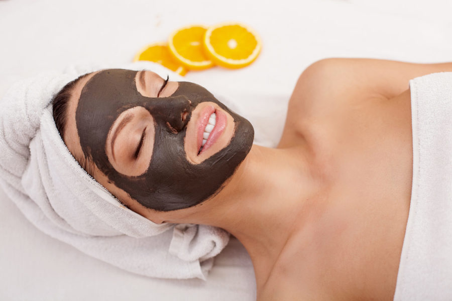 Beautiful Young Woman Is Getting Facial Chocolate Mask At Spa. She Is Lying With Closed Eyes.