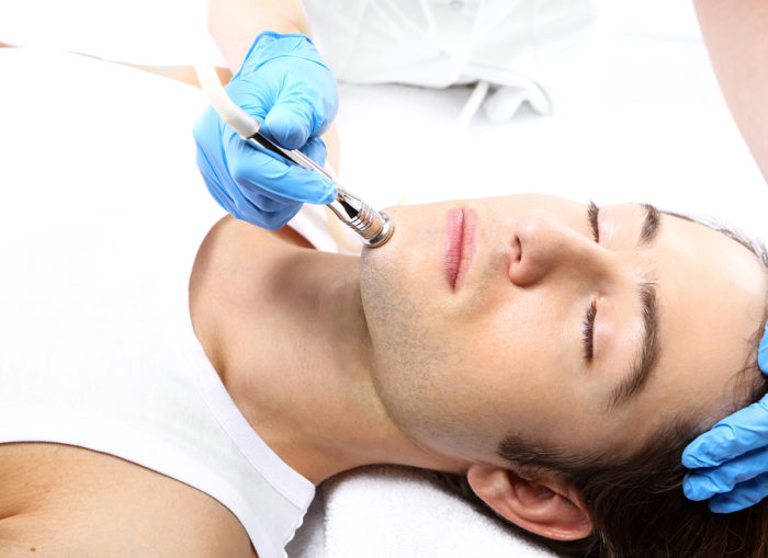 Handsome Man During Microdermabrasion Treatment In Beauty Salon